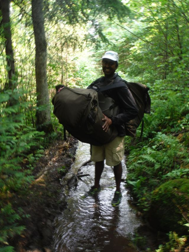 Ravi double packing it. That's my husband! Wading through a wet portage that was more like a stream than a trail.